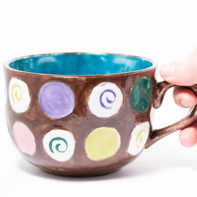 a macro selective shot of a hand grabbing a painted mug in a studio. focus on front of Mug